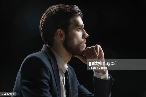 Side view of thoughtful businessman with hand on chin against black background