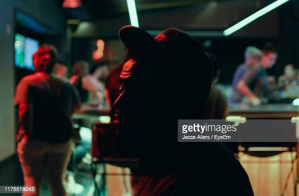 side view of thoughtful man sitting in nightclub - jesse stock pictures, royalty-free photos & images