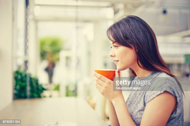 Side view of thoughtful woman holding coffee mug in cafe
