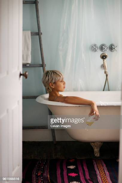 Side view of thoughtful woman holding drink glass while relaxing in bathtub at home