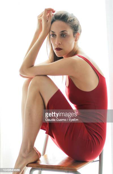 side view of thoughtful woman looking away while sitting on chair against white background - cuomo stock pictures, royalty-free photos & images