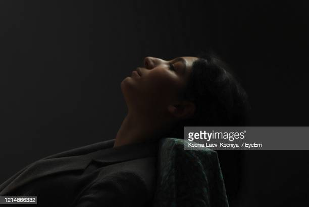 side view of thoughtful woman sitting against black background - 頭をそらす ストックフォトと画像