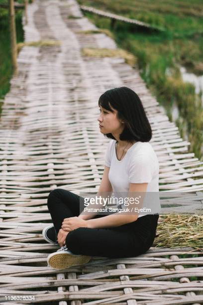 side view of thoughtful woman sitting on boardwalk - pattanasit stock pictures, royalty-free photos & images