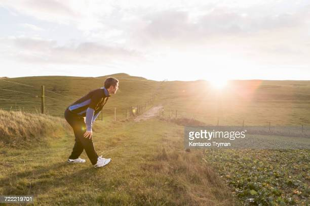 Side view of tired sporty man standing with hand on knee at field during sunny day