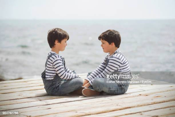 Side View Of Twin Brothers Sitting On Pier Over Sea