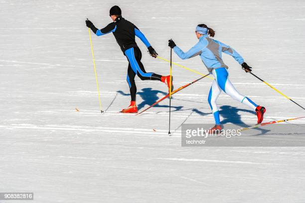 side view of two cross country skiers running in classic technique - close to stock pictures, royalty-free photos & images