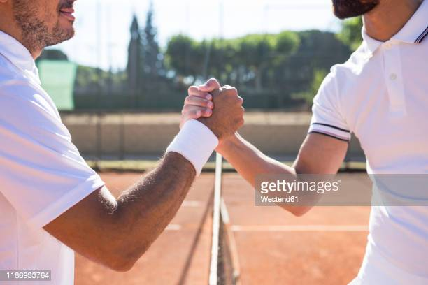 side view of two tennis players with rackets shaking hands and smiling before tennis match - tennis player stock pictures, royalty-free photos & images