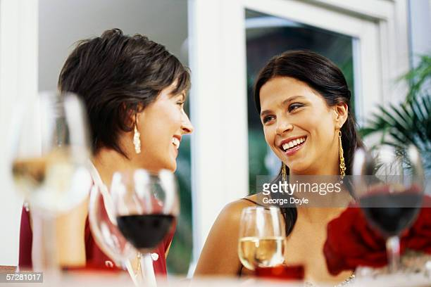 Side view of two young women at a party, drinking wine