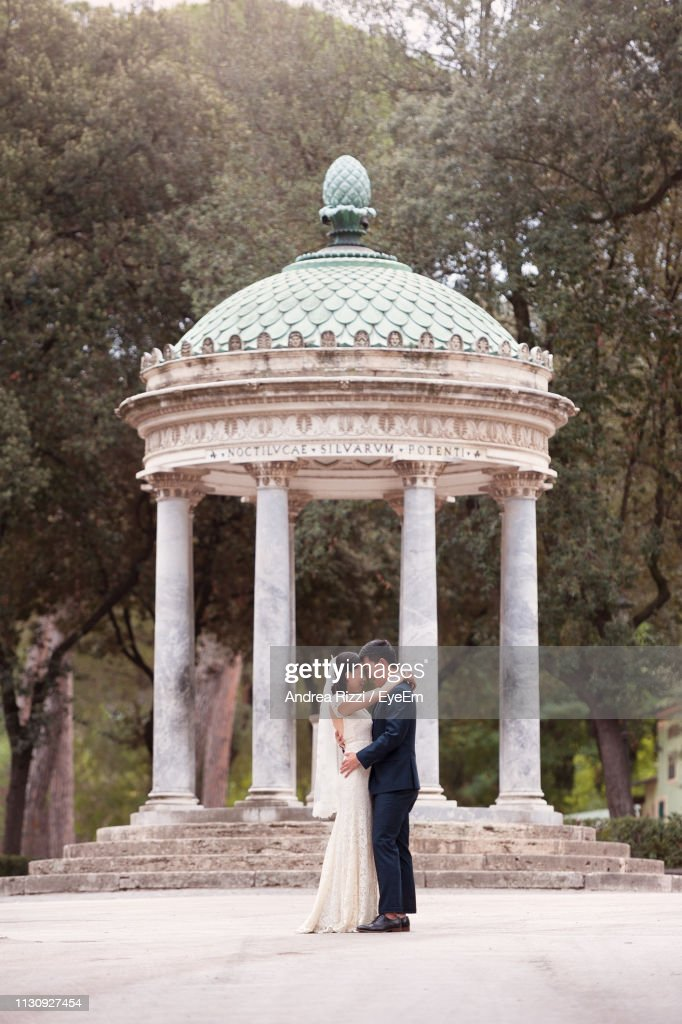 Side View Of Wedding Couple Standing By Gazebo In Park : Foto de stock