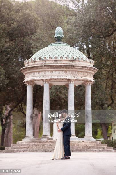side view of wedding couple standing by gazebo in park - andrea rizzi stockfoto's en -beelden