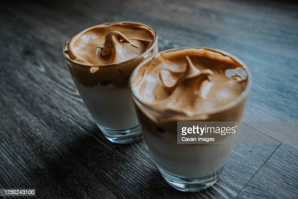 side view of whipped coffee in glass cups on table - dalgona stock pictures, royalty-free photos & images