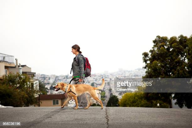 side view of woman and dog walking on street against cityscape - alleen één mid volwassen vrouw stockfoto's en -beelden