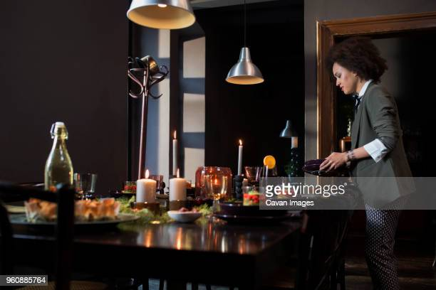 Side view of woman arranging dining table at home during Christmas
