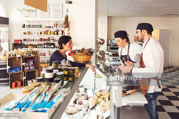 Side view of woman buying grocery from owners at store