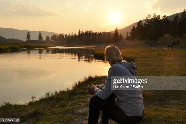 side view of woman by lake against sky during sunset - liga cerina stock pictures, royalty-free photos & images