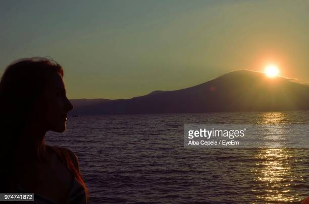 Side View Of Woman By Sea Against Sky During Sunset