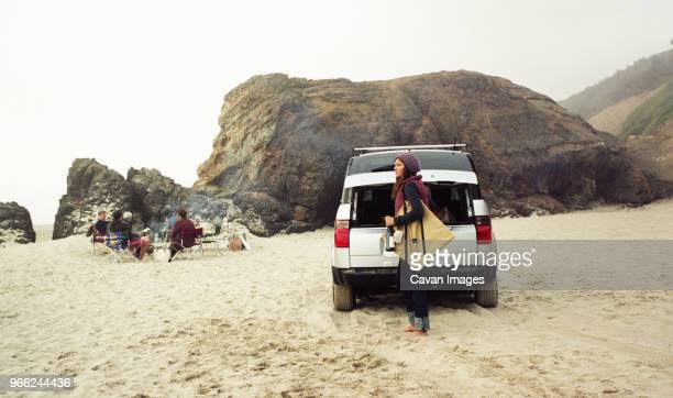 Side view of woman carrying bag by car at beach