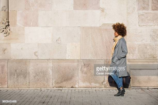 side view of woman carrying bag while walking on footpath by wall - コイリーヘア ストックフォトと画像