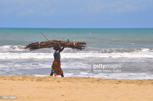 Side View Of Woman Carrying Firewood On Head While Walking At Beach Against Sky
