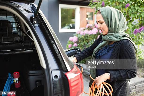 Side view of woman charging electric car while standing outside house
