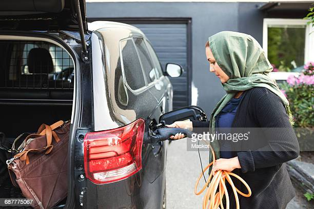 Side view of woman charging electric car with open trunk while standing outside house