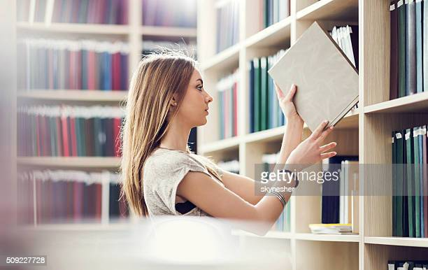 Side view of woman choosing book in a library.