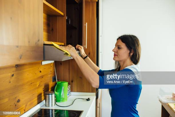 Side View Of Woman Cleaning Air Duct In Kitchen At Home