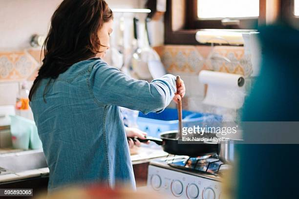side view of woman cooking food in kitchen at home - fornuis stockfoto's en -beelden