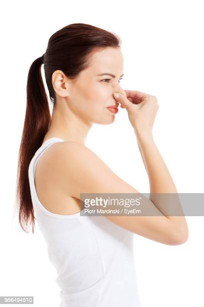 side view of woman covering nose against white background - nariz humano imagens e fotografias de stock