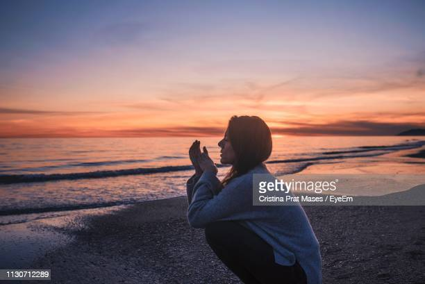 Side View Of Woman Crouching At Beach Against Sky During Sunset