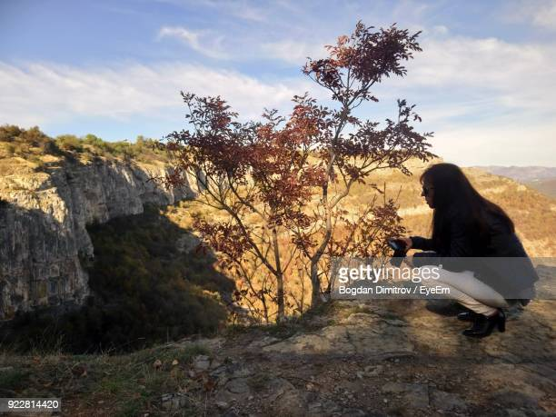 Side View Of Woman Crouching On Cliff Against Sky