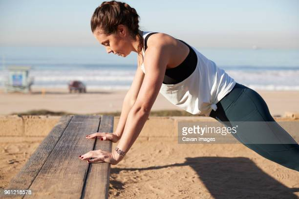 side view of woman doing push-ups on bench at beach - push ups stock pictures, royalty-free photos & images