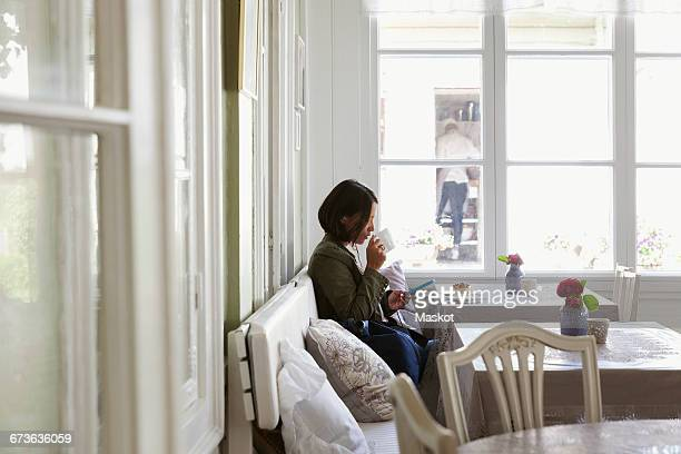 Side view of woman drinking coffee and using phone while resting at cafe