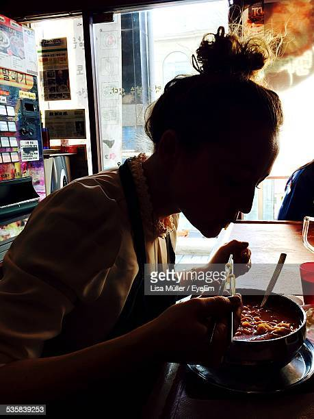 Side View Of Woman Eating Ramen Noodles In Restaurant