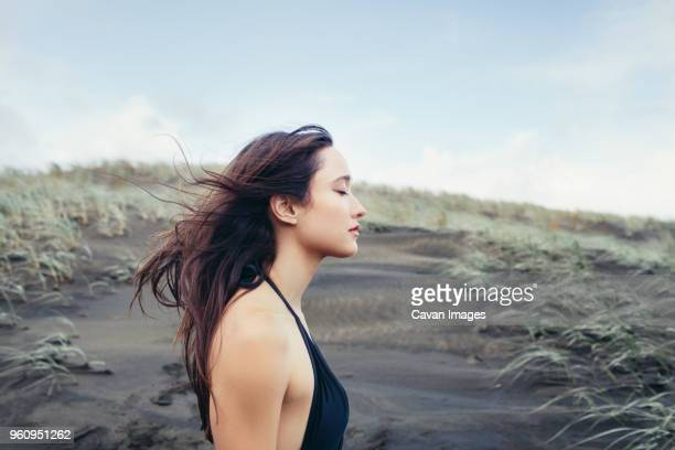 Side view of woman enjoying breeze at Bethells Beach against sky
