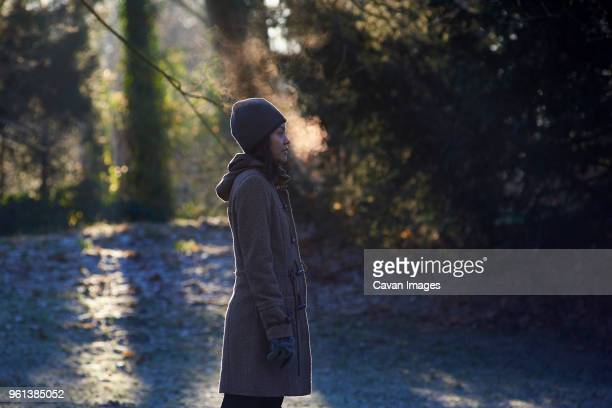 Side view of woman exhaling breath vapor while standing at park during winter