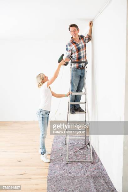 side view of woman giving drill to boyfriend standing on ladder at home - patrick grant stock pictures, royalty-free photos & images