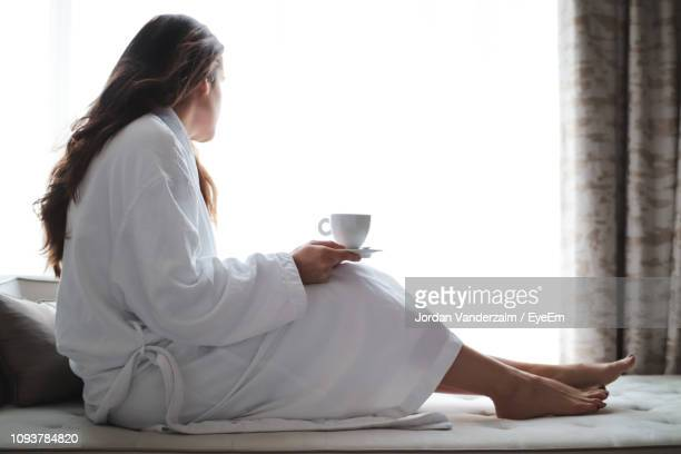 side view of woman having drink while sitting by window at home - bathrobe stock pictures, royalty-free photos & images