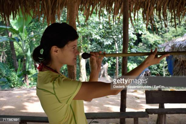 side view of woman holding blowgun at taman negara national park - taman negara national park stock photos and pictures