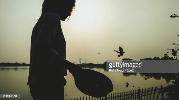 Side View Of Woman Holding Container While Standing Against Lake During Sunset