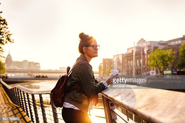 Side view of woman holding disposable cup while standing on boardwalk by river