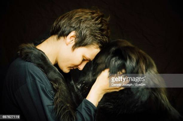 Side View Of Woman Holding Dog Against Black Background