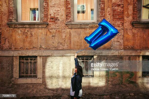Side View Of Woman Holding Helium Balloon Against Old Building