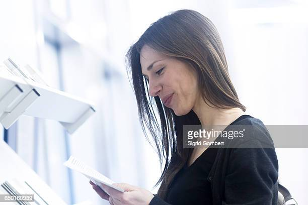 side view of woman holding paperwork looking down smiling - sigrid gombert stockfoto's en -beelden