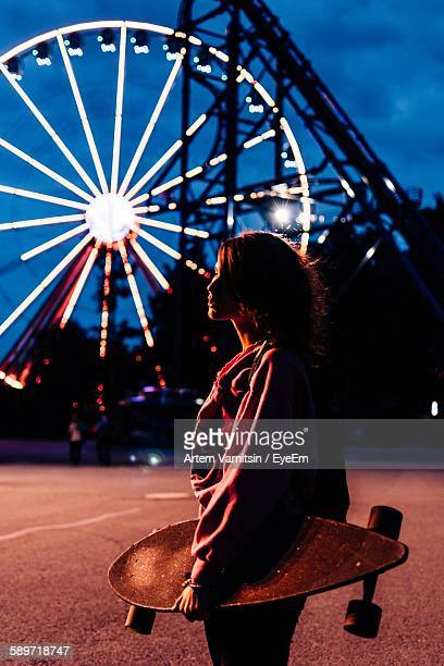 Side View Of Woman Holding Skateboard Against Illuminated Ferris Wheel