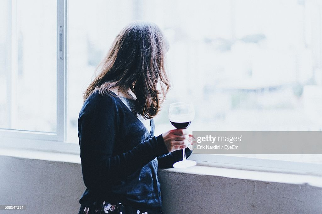 Side View Of Woman Holding Wineglass While Standing By Window : Stock Photo