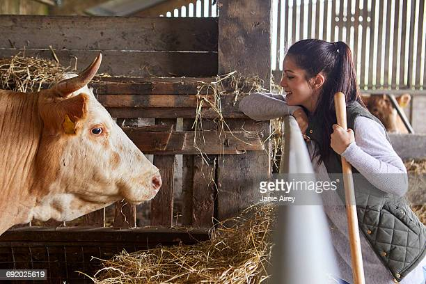 Side view of woman in barn face to face with cow
