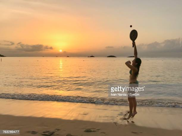 Side View Of Woman In Bikini Playing Matkot At Beach During Sunset