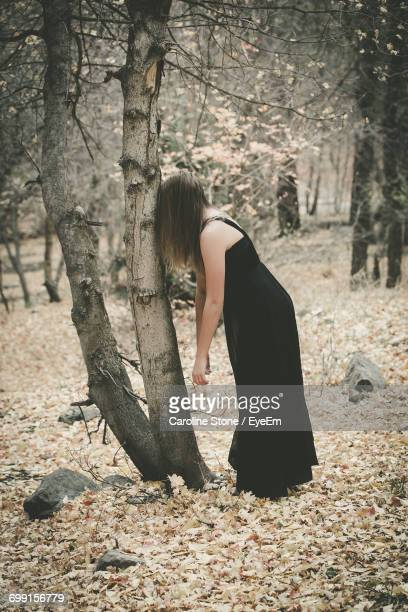 Side View Of Woman In Black Dress Leaning On Bare Tree