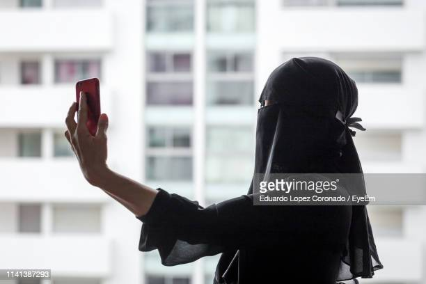 side view of woman in burka photographing by window in city - burka photos et images de collection